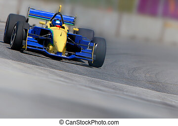 Open wheeled single-seater race car in a corner with limited depth of field