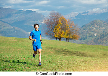 Race in the nature of an athlete in the green meadow