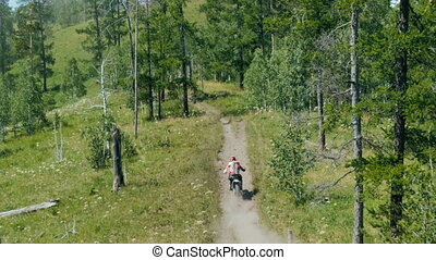 racer a motorcyclist rides along a dusty forest trail during...