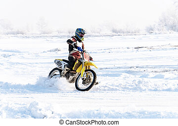 racer on a motorcycle rides in turn of wheels a spray of snow