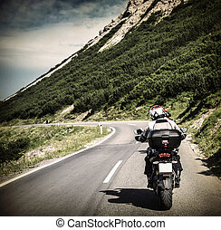 Racer on mountainous highway, biker riding along Alpine mountains, travel to Europe, summer vacation, extreme sport