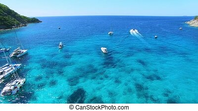 Racha Island Beach. Thailand, Phuket. Yachts , Catamarans and Boats sailing in crrystal clear blue water of ocean. Aerial view. 4K.