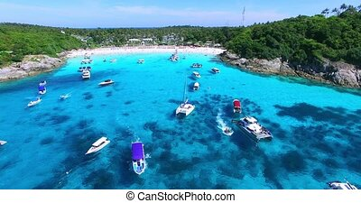 Racha Island Beach. Thailand, Phuket. Yachts , Catamarans and Boats sailing in crrystal clear blue water of ocean. Flying from ocean to sandy beach. Aerial view. 4K.