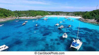 Racha Island Beach. Thailand, Phuket. Yachts , Catamarans and Boats sailing in crrystal clear blue water of ocean. Flying from ocean to sandy beach. Aerial view.
