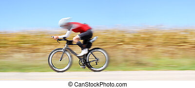 A motion blured bicyclist rides through the countryside on a clear blue sky day