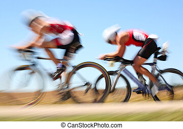 Racing bicycle, motion blur - Two bicyclists ride through...
