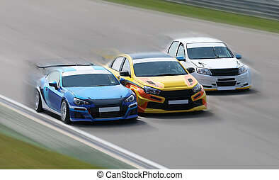 Racing cars on a racing track - Three race cars racing at...
