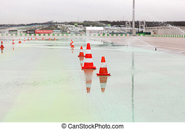 traffic cones and sprinklers on wet speedway