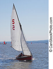 Racing Yacht - A yacht taking part in a race speeds across...