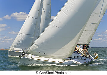 Two beautiful white yachts racing close to each other on a bright sunny day