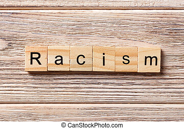 Racism word written on wood block. Racism text on table, concept