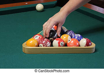Arranging the balls on the pool table to get ready to play