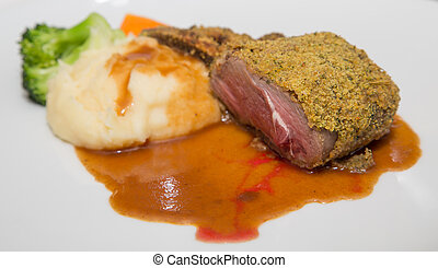 A baked, encrusted rack of lamb on a white plate with potatoes, broccoli and gravy