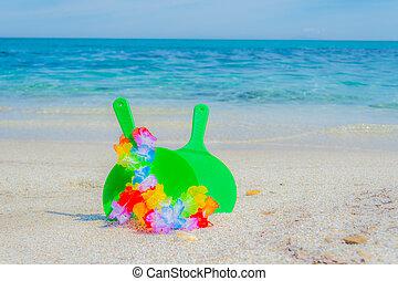 Rackets and hawaiian necklace on the beach