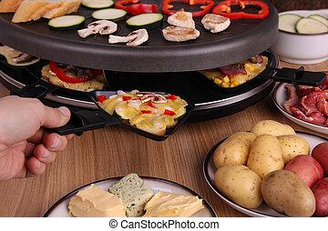 Raclette auf einem Holztisch mit Zutaten