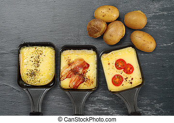 Raclette trays and potatoes - Photo of a three Raclette...
