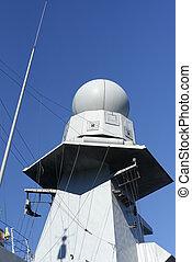 Radar on military ship against blue sky