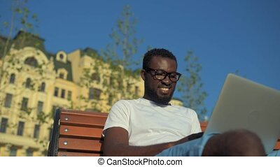 Radiant African American man working with laptop on knees