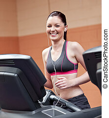Radiant athletic woman with earphones exercising on a running machine in a fitness center