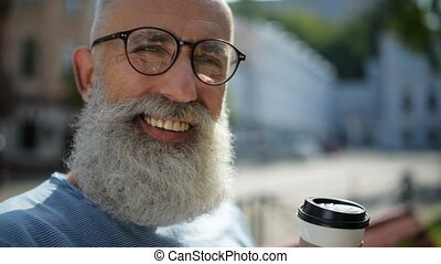 Radiant bearded man with cup of coffee smiling into camera -...