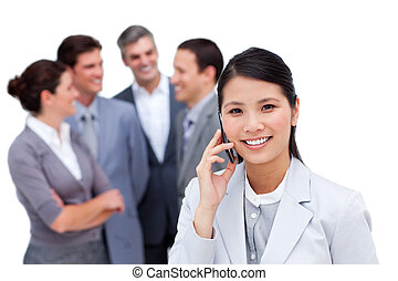 Radiant businesswoman and her cellphone standing apart from her team