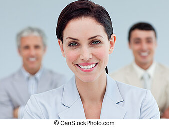 Radiant businesswoman standing in front of her team