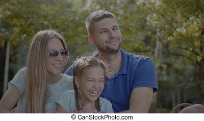 Radiant family with daughter relaxing in park