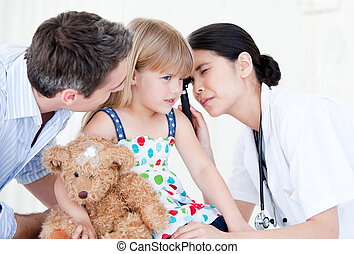 Radiant female doctor examining little girl with medical equipment against white background