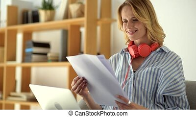 Radiant female freelancer looking at documents while working at home