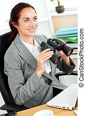 Radiant hispanic businesswoman holding binoculars sitting at her desk in her office