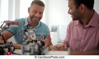 Radiant male colleagues discussing advantages of robotic devise