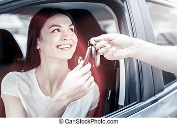 Radiant millennial girl receiving car keys from man