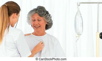 Radiant nurse taking the blood pres
