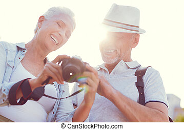 Radiant senior couple looking at photos on camera