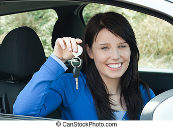 Radiant teenager holding car keys sitting in her new car smiling at the camera