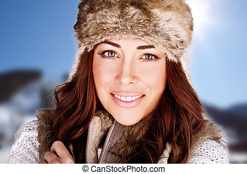 Radiant Winter Beauty. Beauty shot of a radiant smiling woman full of vitality and with a lovely complexion., against blue sky