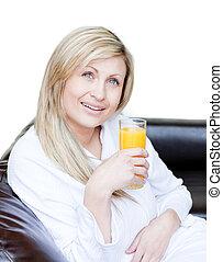 Radiant woman drinking an orange jus