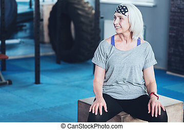 Radiant woman sitting on box while resting in gym