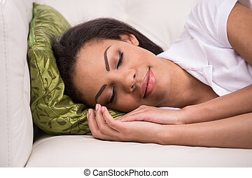 Radiant woman sleeping on sofa in living room. Young African...
