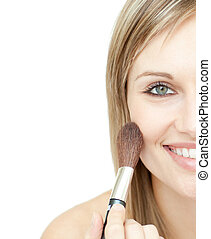 Radiant woman using a powder brush against a white...