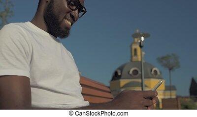 Radiant young gentleman using smartphone outdoors -...