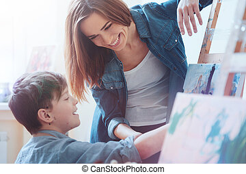 Radiant young woman helping youngster with new masterpiece