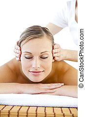 Radiant young woman receiving a head massage