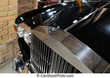 Radiator grill and headlights of black vintage classic car auto