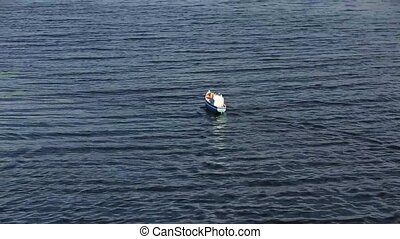 Radio controlled toy boat racing on a dark blue water surface. Small waves on lake. Hobby concept. Sweden
