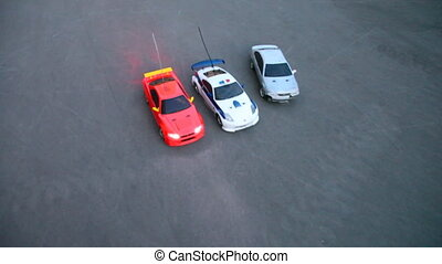 Radio-controlled toy cars start and go out of frame on...