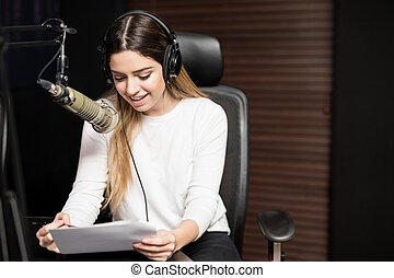Radio host broadcasting a show in studio