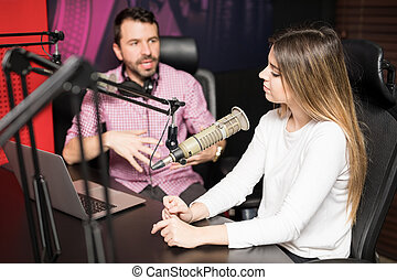 Radio hosts moderating a live show at station