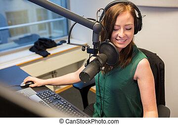 Radio Jockey Smiling While Wearing Headphones In Studio