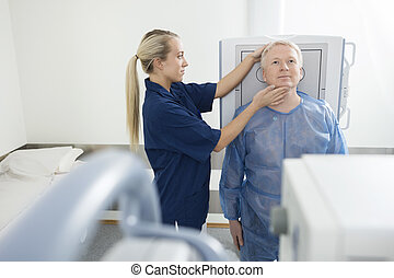 Radiologist Adjusting Head Of Patient Before Taking Xray In Clin